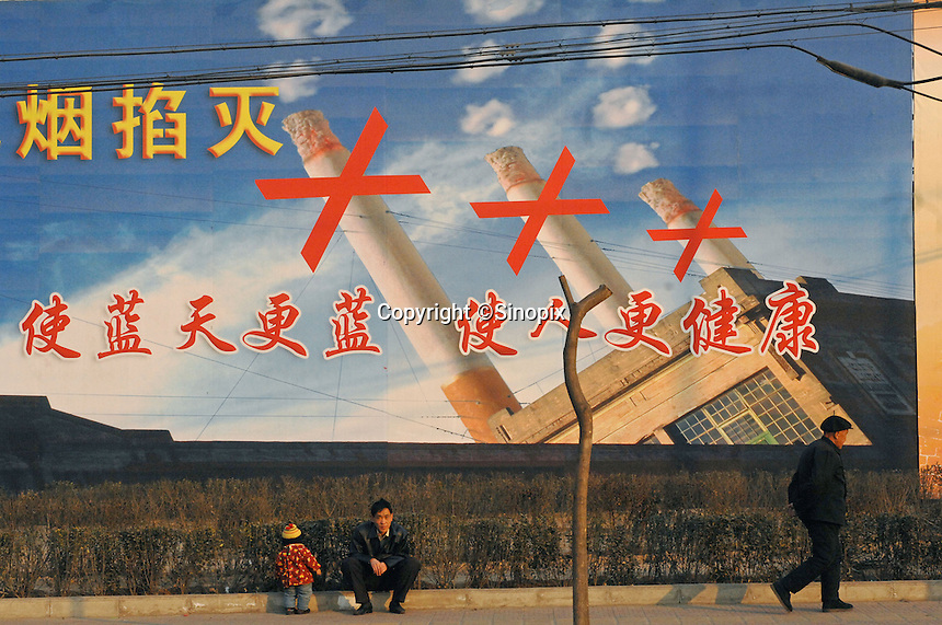 A child pees in front of an anti-smoking propaganda billboard in Linfen city, Shanxi province, China..