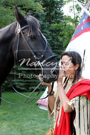 Native American Indian woman bonding with her horse by breathing into his nose
