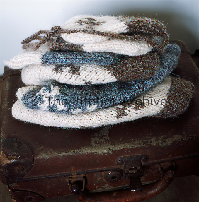 Knitted items are placed on a battered suitcase.