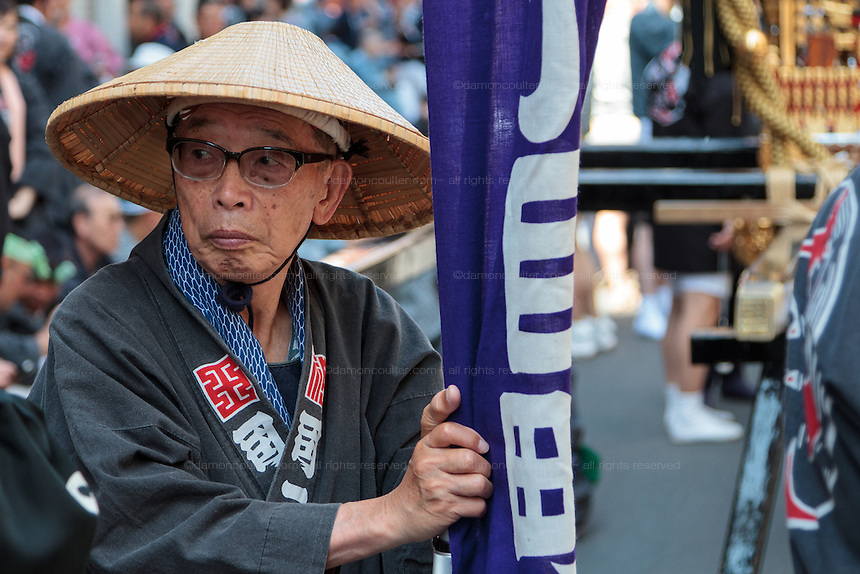 A man in a traditional festival hat poses by a mikoshi, or portable shrine, in the bi-annual Kanda matsuri (festival). Chiyoda Ward, Tokyo, Japan Sunday May 10th 2015. Over 200 mikoshi are carried through the streets of central Tokyo every 2 years in this spring festival