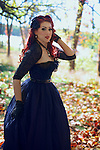 Young woman wearing regency dress<br /> A beautiful redhead poses in the forest in her fancy regency ballgown, with autumn leaves all around