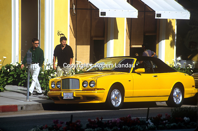 Yellow Rolls Royce parked in front of Bijan boutique on Rodeo Drive in Beverly Hills, CA
