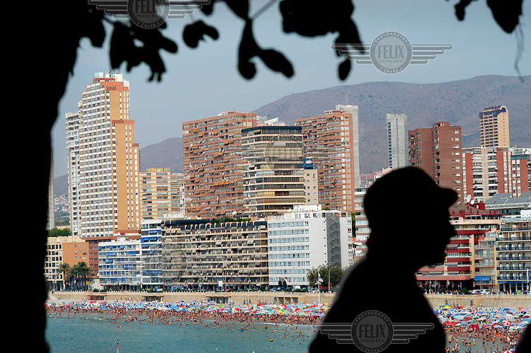 Tourists crowded on Poniente beach, with rows of hotel skyscrapers behind.