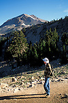 Hiker on trail to Bumpass Hell below Mount Lassen volcano peak, Lassen Volcanic National Park, California