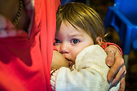 Close-up of a child of about 18 months breastfeeding while looking at the camera.