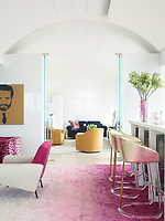 The luxurious penthouse apartment is full of edgy chic and sizzling colour. In the living room the circa-1958 two-toned armchair is by Pierre Guariche and the Lucite barstools are from the 1970s. The custom-made silk shag rug is by Beauvais Carpets.