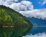 British Columbia, Canada: View of cloud wrapped mountains above the calm, reflecting waters of Homfray Channel, Desolation Sound
