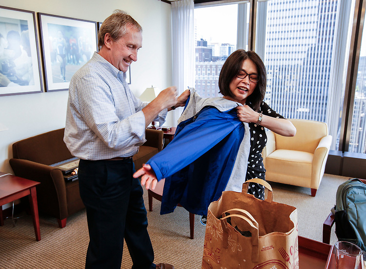 Bob Janis, vice president of facility operations, presents Josephine Esteban a jacket before a tour of the Loop Campus Wednesday, July 5, 2017. The Estebans spent an hour getting acquainted with some of the spaces and faces in the Loop during Dr. Esteban's first week on the job.  (DePaul University/Jamie Moncrief)