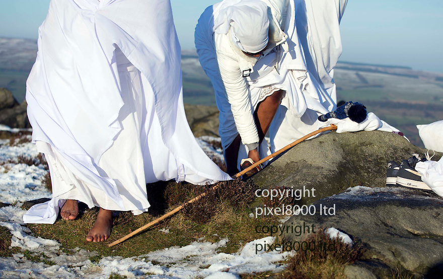 Pic shows: Ilkley Moor snow scene today<br /> Worshippers from the Church of the Apostles climb on top of the famous Cow and Calf rocks to be &quot;nearer to God&quot;.<br /> <br /> They braved the minus temperatures to offer up their prayer in bare feet and clad in white robes.<br /> <br /> Baffled walkers looked on at they carried out their ritual on the snow covered moor.<br /> <br /> <br /> <br /> <br /> Pic by Gavin Rodgers/Pixel 8000 Ltd