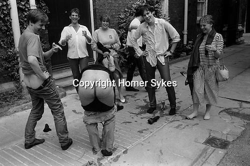 Drunk Cambridge University students. Man Mooning friends having fun. Cambridge 1980s.