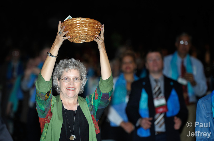 A woman helps collect the offering during the April 24 opening worship service of the 2012 United Methodist General Conference in Tampa, Florida.