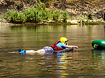 Inflatable canoe pulling  paddle boarder on the Lower Salmon River, central Idaho