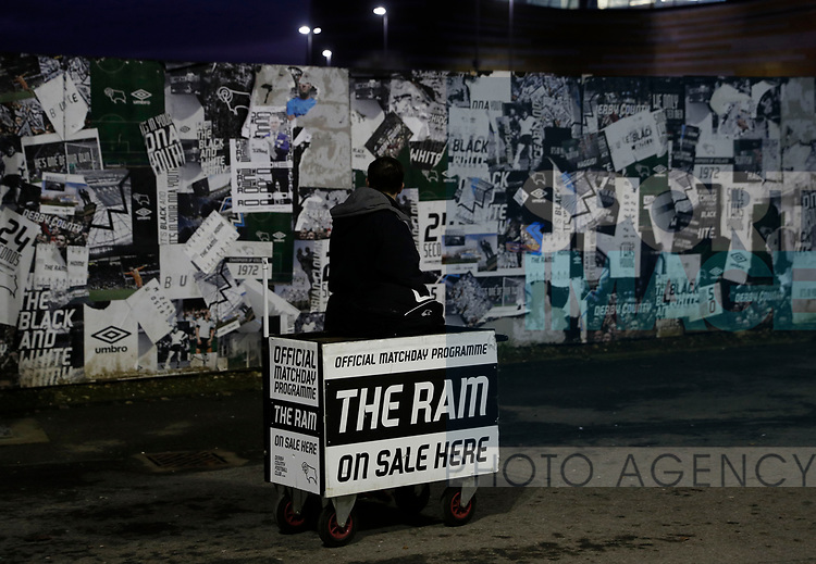 Programme seller sets up opposite a wall with peeling posters on it during the FA Cup match at the Pride Park Stadium, Derby. Picture date: 4th February 2020. Picture credit should read: Darren Staples/Sportimage