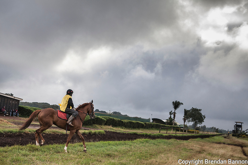 Work rider and retired jockey Steve Njuguna rides out in the morning  as golf caddies look at  at the Ngong Racecourse in Nairobi, Kenya. March 15, 2013. Photo: Brendan Bannon