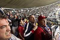 USA fan watch out for thrown objects thrown by Mexican fans at the  American supporters section protected by Mexican police at Azteca stadium after the USA played Mexico in a  World Cup Qualifier in Mexico City, Mexico on March 26, 2013.  The man in the lower left hand of the image was bleeding after being hit by a flying object.