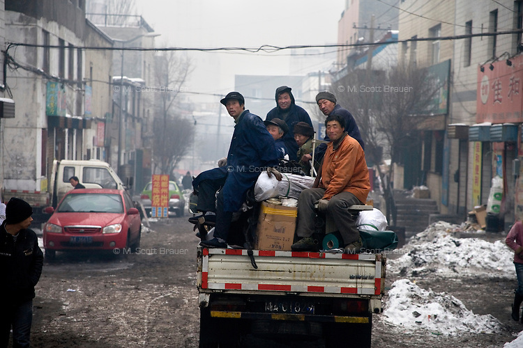 Workers ride on a truck in a Han neighborhood of Urumqi, Xinjiang, China. The city is divided between Han and Uighur ethnicities, and violent clashes erupted between the groups in 2009.