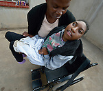 Tendai Nyamkondiwa lifts her niece, Ngonidzashe Rondozai, into a wheelchair in Harare, Zimbabwe.  Rondozai, 17, has cerebral palsy, and Nyamkondiwa, her aunt, is her primary caregiver. Rondozai uses an appropriately designed and fitted wheelchair provided by the Jairos Jiri Association with support from CBM-US.
