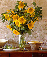 In a country dining room sunflowers glow against the mellow grey stones of the rustic walls