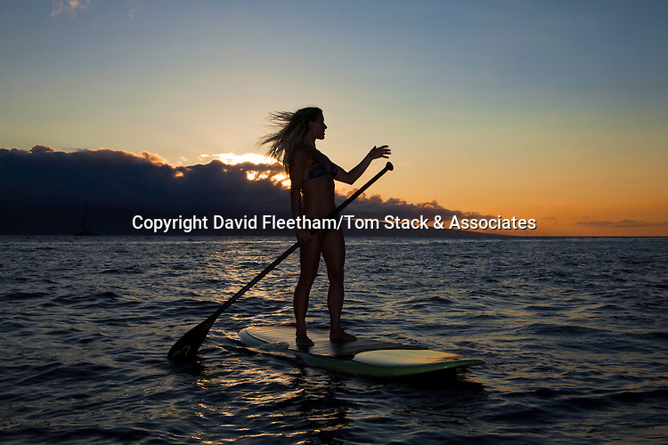 Surf instructor Tara Angioletti at sunset on a stand-up paddle board off Canoe Bearch, Maui. Hawaii.  Image is model released.
