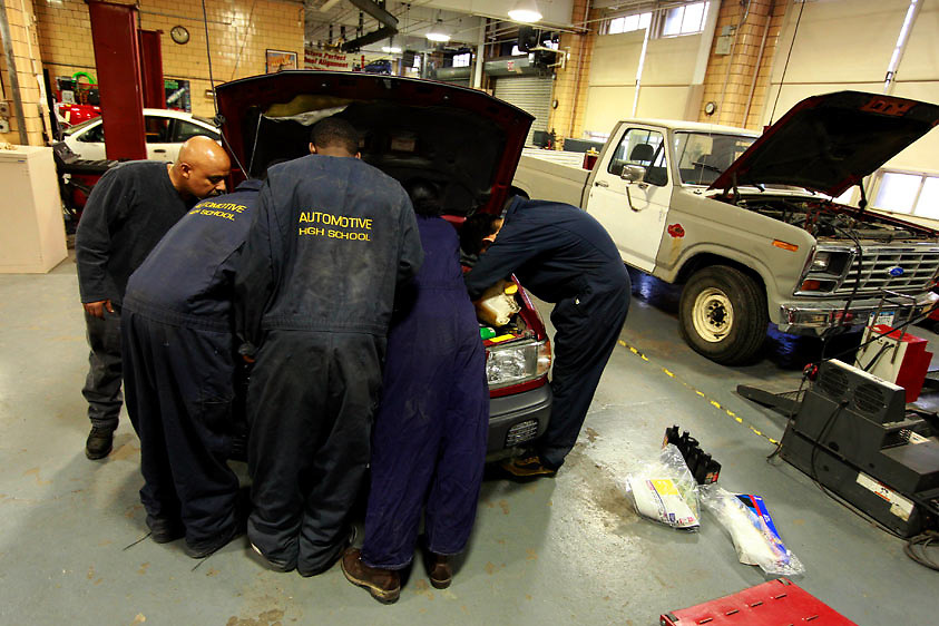 Automotive HS, Brooklyn, NY on Friday, January 22, 2010.  High school students have the opportunity to participate in a special program where they perform basic maintenance and repairs on privately owned cars at very competitive prices.  Under the tutelage of teacher Carlo Caraballo, far left, a group of students perform a tune-up on a car.