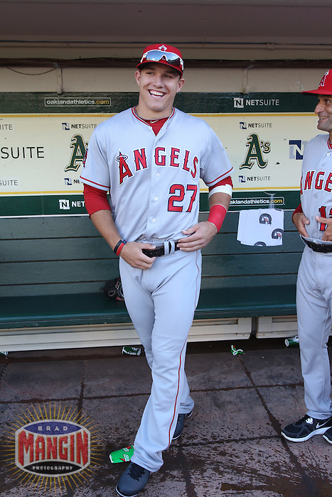 OAKLAND, CA - AUGUST 6:  Mike Trout of the Los Angeles Angels laughs in the dugout with coach Dino Ebel before the game against the Oakland Athletics at O.co Coliseum on Monday, August 6, 2012 in Oakland, California. Photo by Brad Mangin