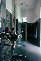 In the bathroom the walls of the walk-in shower are clad in black-and-white marble with a circular stainless steel wash basin on an adjacent wall