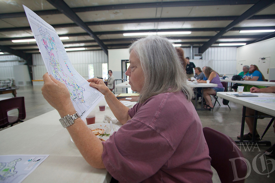 RYAN MCGEENEY/Arkansas Democrat-Gazette --06-26-2014-- Carolyn Griffith of West Fork examines a map of the seven sub-watersheds that make up the Beaver Lake Watershed during a public meeting Thursday evening at the West Fork Community Center. The meeting was one of a <br />