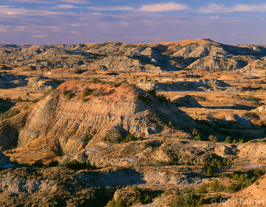 NDTR_120 - USA, North Dakota, Theodore Roosevelt National Park, Evening light defines eroded, sedimentary hills and grassy plains in autumn, Painted Canyon Overlook, South Unit.