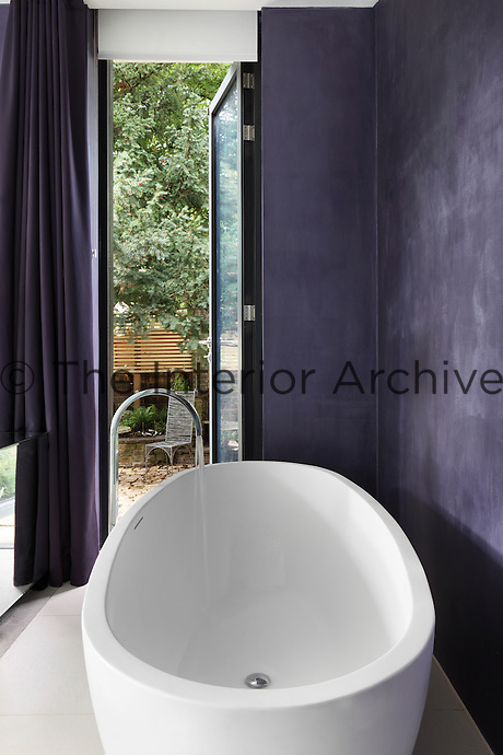 A purple bedroom with a freestanding bath within the room. A full height glass door leads to the garden beyond.