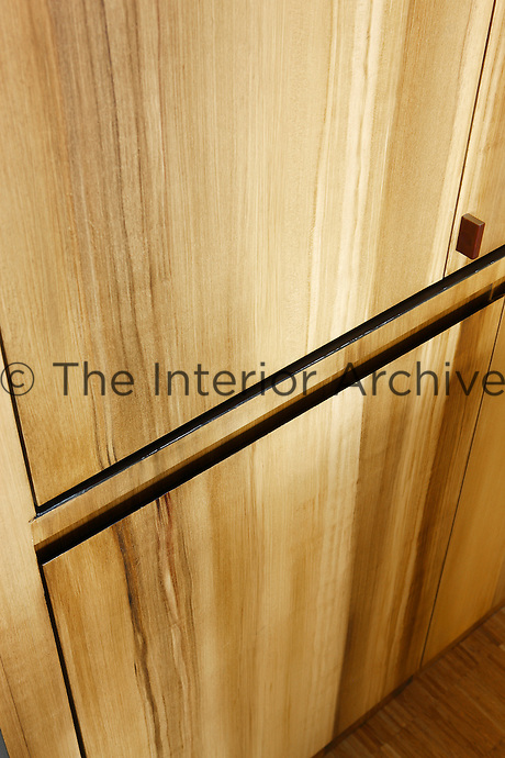 Kitchen cupboards painted a wood grain effect conceal the various appliances