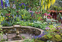 Colorful mixed perennial flower garden with Delphinium, sempervivum rock garden, bird bath, and climbing plants, circular sunken patio, raised beds, Laburnum tree, blue,yellow, red, pink colors