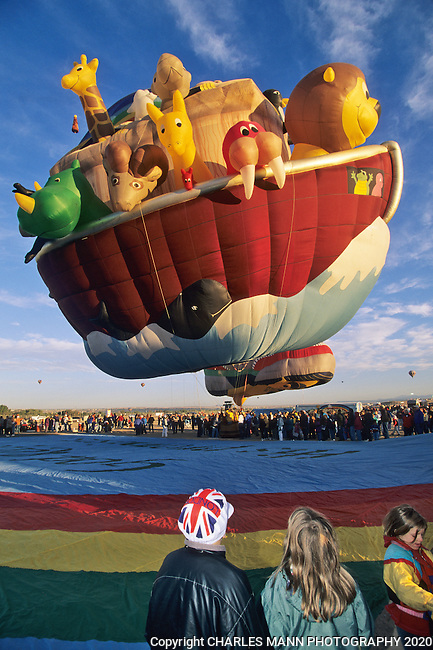 At the Albuquerque International Hot Air Balloon Fiesta a Noah's Ark of colorful animals entrances some youing visitors as it rises on teh day of a mass asencion.m