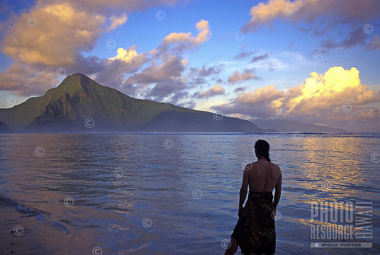 Man stands on Ofu Island beach at sunset, with view of Olosega. American Samoa