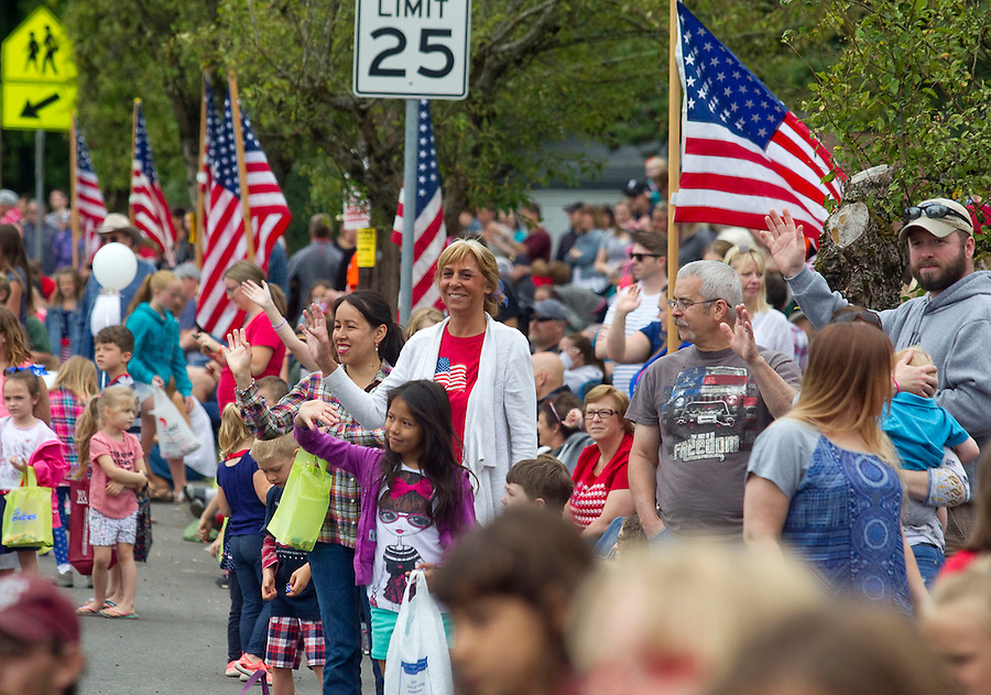 Spectators wave at passing floats at the Fourth of July Parade through the town of Ridgefield Monday July 4, 2016. (Photo by Natalie Behring/ for the The Columbian)