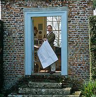 Portrait of furniture designer Thomas Messel standing in the door of his summer studio