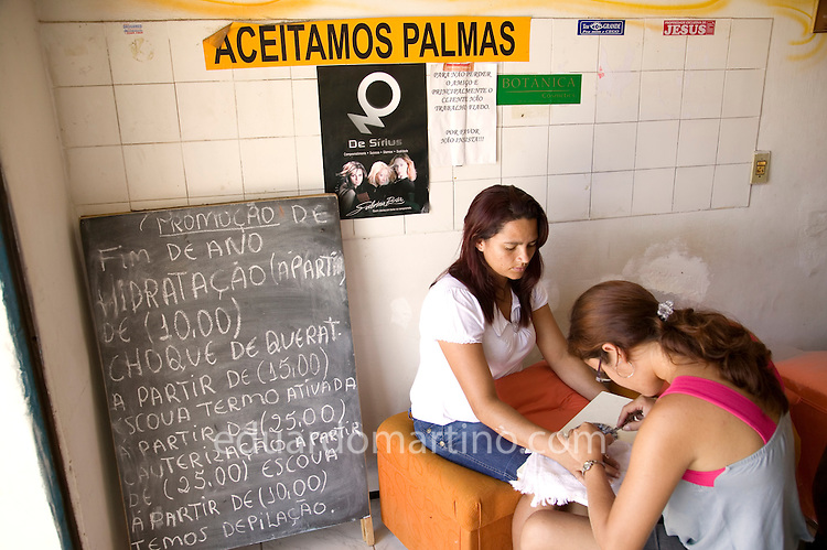 "Detail of a sign ""we accept Palmas"" in a shop front in Conjunto Palmeiras, Fortaleza, Ceara, Brazil.Photo: Eduardo Martino / Documentography"