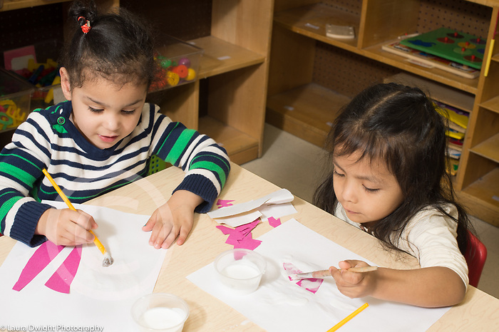 Education Preschool 3 year olds art activity gluing collages two girls using paintbrushes to apply glue using opposite hands