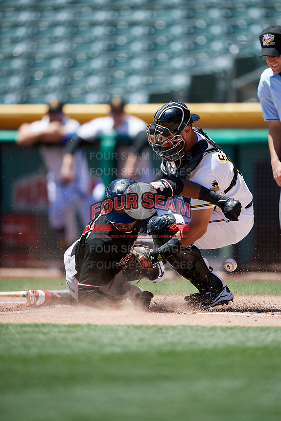 Tony Sanchez (27) of the Salt Lake Bees on defense as a sliding Rosell Herrera (7) of the Albuquerque Isotopes makes it under the tag in Pacific Coast League action at Smith's Ballpark on June 11, 2017 in Salt Lake City, Utah. The Bees defeated the Isotopes 6-5. (Stephen Smith/Four Seam Images)