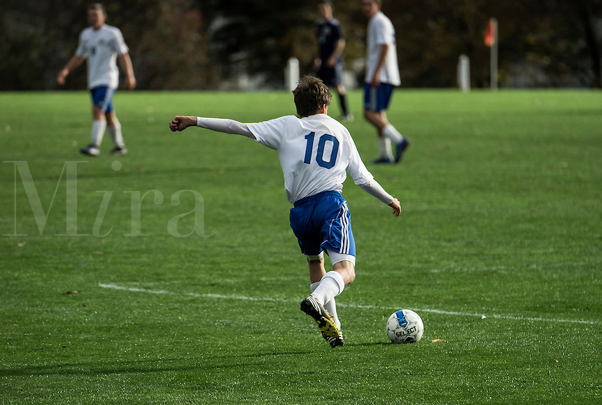 Youth soccer player takes a free kick during a game.