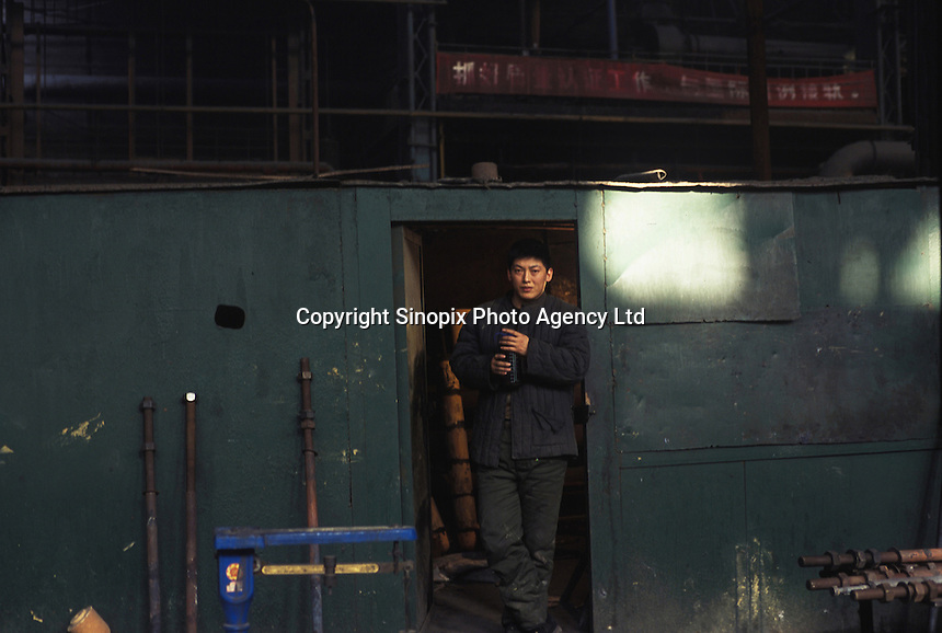 A worker rests in a workshop of a state cast steel factory in Tiexi industrial area, Shenyang, northeast China..20-JAN-02