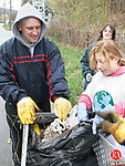 TORRINGTON, CT- 22 APRIL 2006- 042206JW06.jpg  -- Torrington High school Civics Club student advisor Patrick Richardson helps club member Lindsay Boyer dump some trash as club member Danielle Fantozzi looks on. The club cleaned South Main Street in Torrington Saturday morning during Earth Day clean-up with the help of two abandoned shopping carriages, one of which they pulled from the Naugatuck River.  Jonathan Wilcox Republican-American