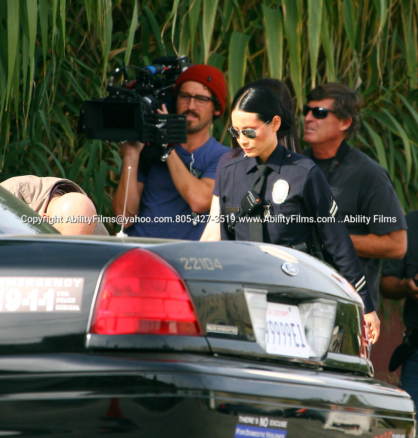 ...November 28h 2011..Lucy Liu dressed as a cop police officer while filming the tv show South Land in Los Angeles California. Lucy was holding a EL Pollo Loco cup ..AbilityFilms@yahoo.com.805-427-3519.www.AbilityFilms.com
