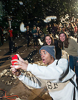 "From left, Deon Summerville '16, Jessie Fontana-Maisel '16 and Maddy Farkas '16 take a picture under the ""snow"". Photo from Occidental College's annual Winter Fair, featuring snow in the quad, holiday crafts, a gingerbread house-making contest, music and holiday treats like hot chocolate, latkes, and french toast. December 4, 2013 in the Academic Quad. (Photo by Marc Campos, Occidental College Photographer)"