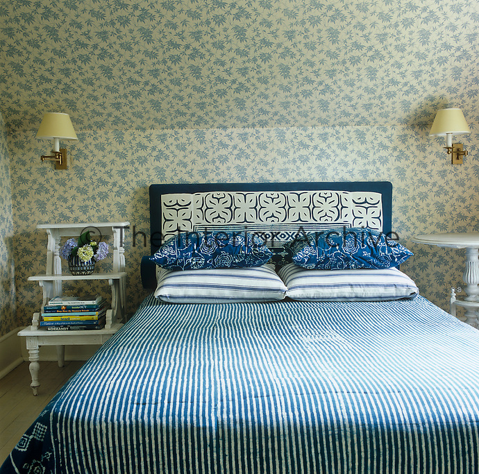 The bed's headboard, pillow shams and cover are made from Indian batiks and the walls are covered in blue and white floral fabric