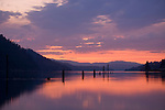 Idaho,North,Lake Coeur d'Alene, Wolf Lodge Bay. Pink and purple sky reflections in the calm waters with rustic pilings.