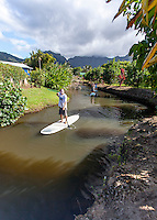 Caucasian male and others stand up paddleboarding on the Hanalei River, Kaua'i