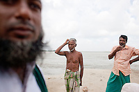 Local villagers stand on the bank of river Padma.  Every year in Bangladesh, millions of people are affected by river erosion that destroys home, farmland, communication infrastructure. In the last couple of days erosion by the Padma River has caused extensive damages to houses, agricultural lands, roads etc. In Dohar, lots of people lost their lands and homes due to Padma river banks erosion. Dohar, Dhaka, Bangladesh.