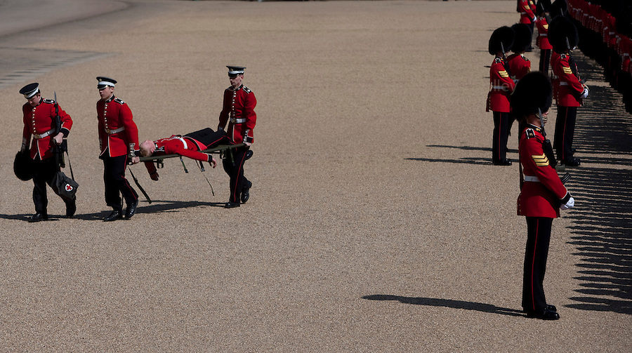 """Mcc0023074 . Daily Telegraph..A Grenadier Guard is taken off by stretcher bearers after """"piling in"""" whist rehearsing on Horseguards for Trooping the Colour in celebration of the Queen's Birthday on June 12 ..The Grenadier Guards only recently finished a six month tour of Helmand , Afghanistan on March 31...London 19 June 2010......Not AP.Not Reuters.Not PA.Not Getty.Not AFP."""