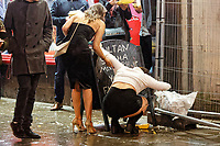 Pictured: A woman throws up in Wind Street, Swansea, south Wales, UK. Friday 21 December 2018<br /> Re: Black Eye Friday, also known as Mad Friday or Black Friday which is the last Friday before Christmas Day.