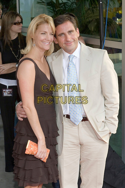 "NANCY WALLS & STEVE CARELL.""The 40 Year-Old Virgin"" Premiere,.held at The Arclight Cinema,.Los Angeles, 11th August 2005.half length beige suit white shirt blue tie broen layer ruffle dress orange clutch bag silver earrings hand waist.www.capitalpictures.com.sales@capitalpictures.com.© Capital Pictures."